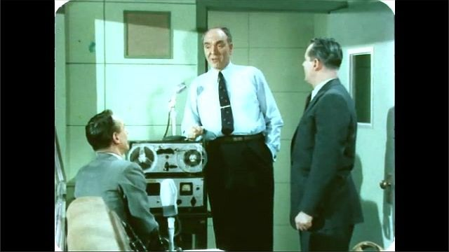 1960s: Man in recording booth talks. Man walks into recording booth, men talk. Conductor speaks with violinist, orchestra takes their seats.
