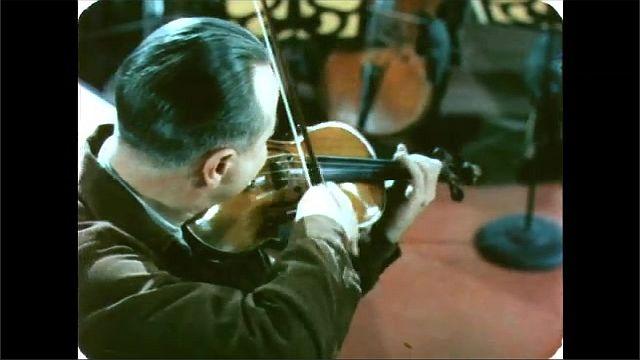 1960s: Man plays violin.