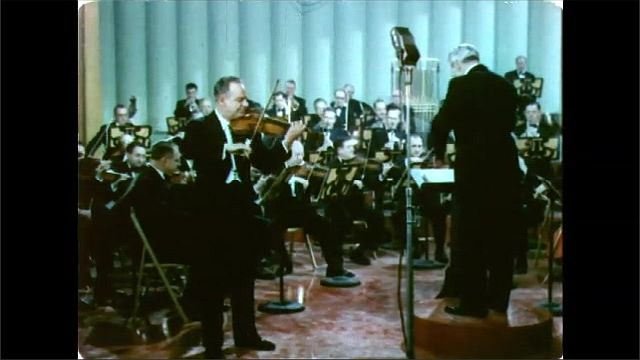 1960s: Man plays violin, Orchestra plays music. Conductor conducts.