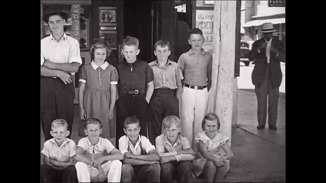 1950s: Children and teens pose in large group. Women and men stand outside store.