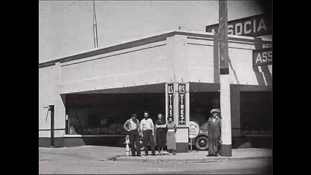 1950s: Man climbs tall tree, cut off top of tree. People stand outside tire store. Car parked on street.