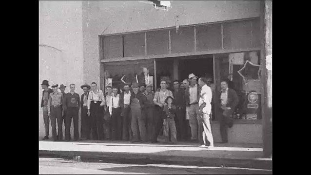 1950s: Men stand outside club. Sprinklers spray crops.