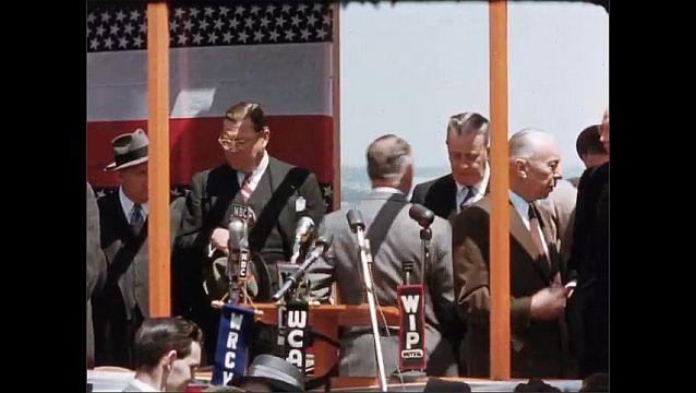 1950s: Women practice baton twirling near truck. Men walk onto stage. Man speaks into microphones.