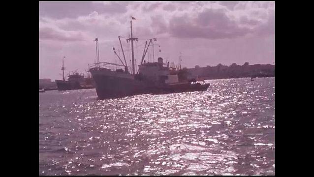 1960s: Boats move through harbor.  City.