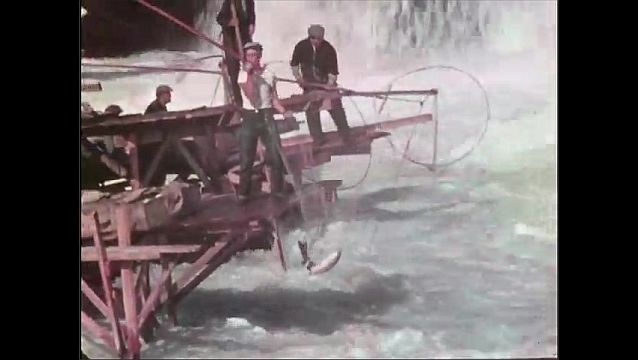 1940s: People ride horses alongside body of water. Men cast fishing nets near waterfall.
