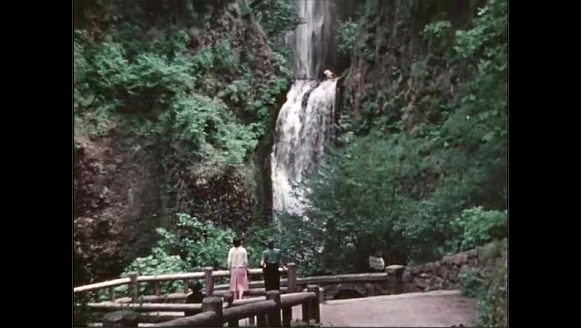 1940s: View of mountains with bridge in foreground. Women walk along observation deck near waterfall. Panorama of waterfall.