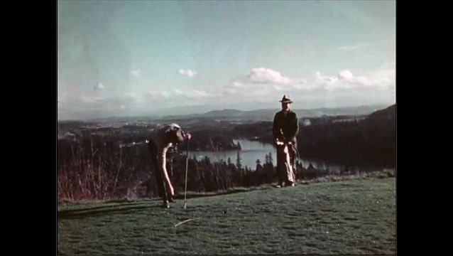 1940s: Men golf on hilltop. People golf next to body of water.