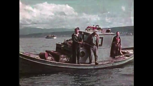 1940s: Fish wriggle. People in boats on the water. Fish jump in water.