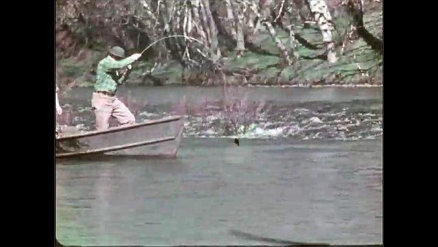 1940s: Boat navigates rapids. Men fish. Fish flops around in water.
