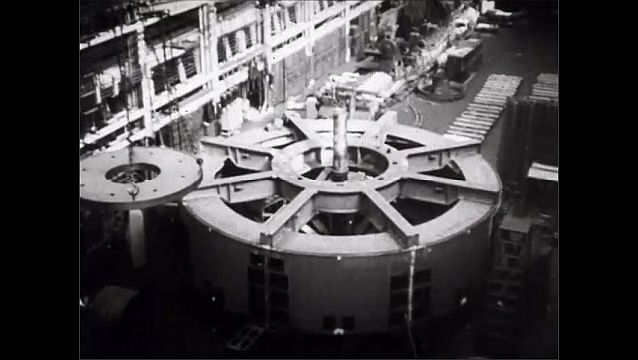 1940s: Model of the Boulder (Hoover) Dam with engineers surrounding. Enormous electric turbines are constructed.