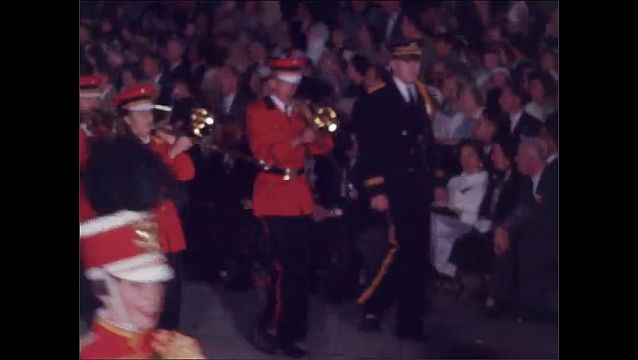 1960s: Drum majorettes march in parade. Band plays and marches. Women wave from parade float.