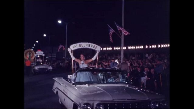 1960s: Women seated on parade float, waving, with young girl standing at front. Miss Delaware waves from convertible in parade. Woman standing on parade float waves.