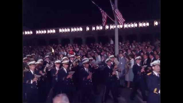 1960s: Color guard marches in parade. Marching band performs in parade.