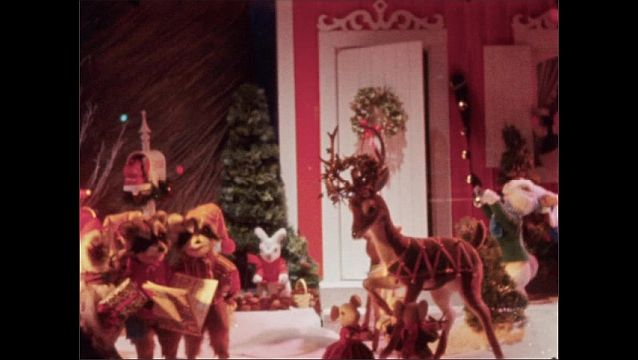 1960s: NEW YORK, UNITED STATES: snowflake lights in street. Animatronic Santa and deer by house. Santa opens door of house and waves