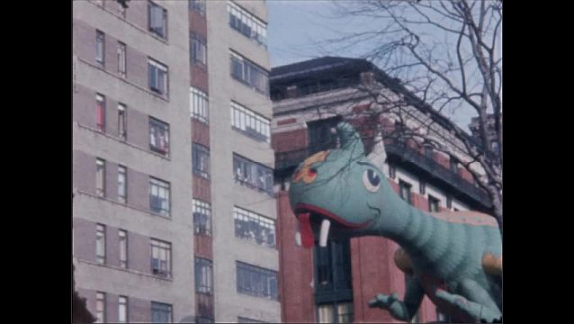 1960s: NEW YORK, UNITED STATES: buildings in New York. Inflatable dinosaur in street parade.