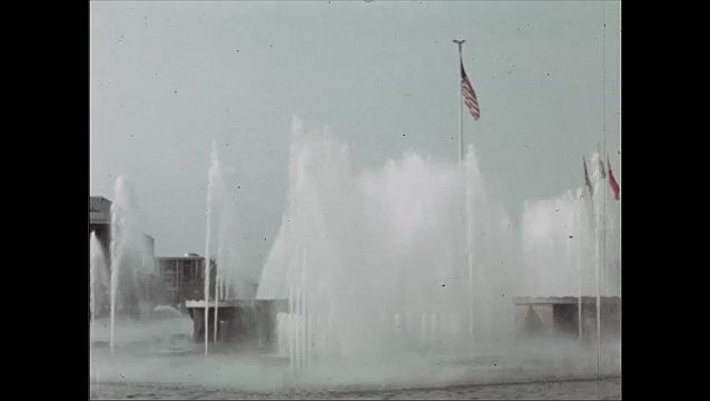 1930s: Flags of various countries. Water fountains, pool of water. People walk around in front of world's fair pavilions.