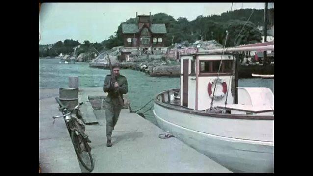 1940s: Man exits room. Man picks up rifle from boat, walks down dock. Man picks up rifle, man gets on bike.