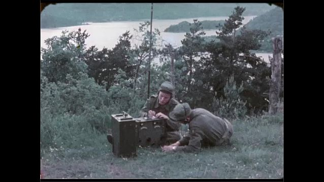 1940s: Soldiers walk through forest. Soldiers use communications equipment at top of hill. Soldier paces in front of building in city.
