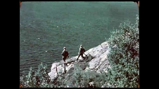 1940s: Soldiers row boat on water. Soldiers climb down mountain, stand on rocks, look out over water. Soldiers position themselves behind shield of large caliber gun, aim gun.