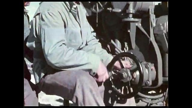 1940s: Men maneuver large caliber weapon into position, aim weapon towards sky.
