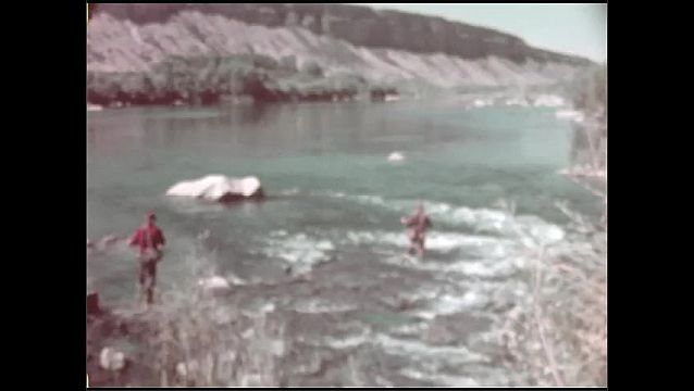 1950s: High angle, men fishing in river.