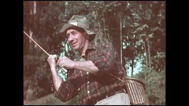 1950s: Man in river, pulling on fishing line. Man fishing in river. Close up of man. Line pulls fish in water. Man fishing. Close up of man. Line pulling fish. Man reeling in fish. Fish in water.