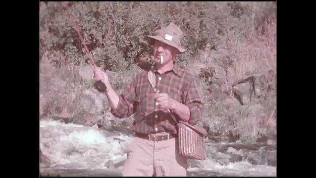1950s: Man fishing in river. Long shot, man fishing. Man in river. Figh caught on line. Man in river. Man in river. Fish pulling on line. Long shot of man.