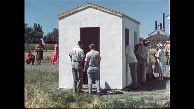 1960s: UNITED STATES: panels on wooden shed. Wood pile in shed. People look inside different sheds. Pit by shed.