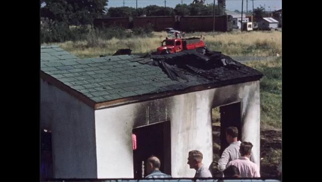 1960s: UNITED STATES: general public attend fire session. People look at damage from fire. Roofs of sheds after fire.