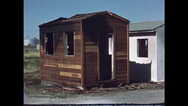 1960s: UNITED STATES: sheds in row in field. Damage to sheds from fire.