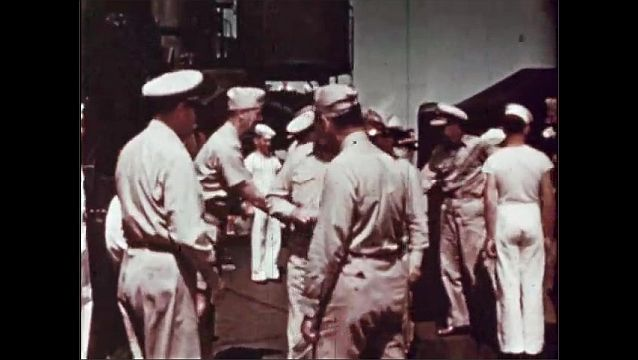 1940s: UNITED STATES: sailors on deck of ship. McKinley battle ship. Men from Navy shake hands on deck. Navy Secretary.