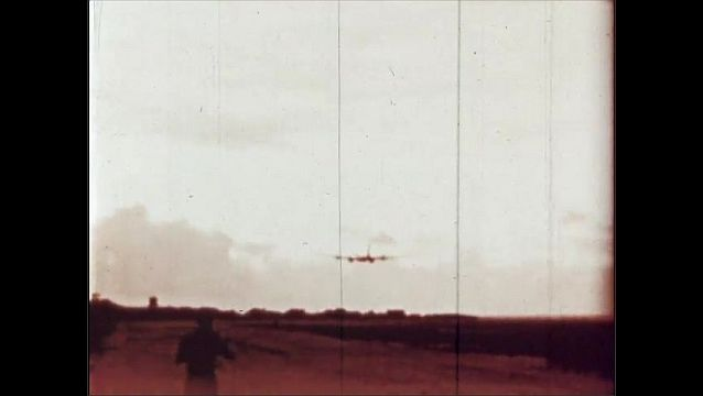 1940s: UNITED STATES: plane flies above ground. Photographic plane in sky