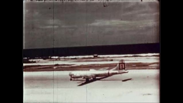 1940s: UNITED STATES: plane flies over base. Plane returns to base after dropping bomb. Airforce photographic planes.