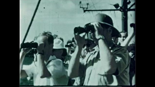 1940s: UNITED STATES: automatic firing board. Man broadcasts to observers. Observers with goggles wait for blast