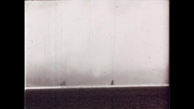 1940s: UNITED STATES: nuclear explosion on island. Explosion on horizon. Mushroom cloud over island.