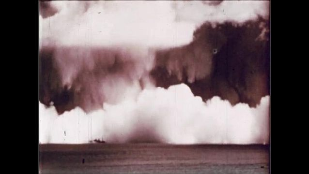 1940s: UNITED STATES: water from columns hits ships. Target fleet and cloud