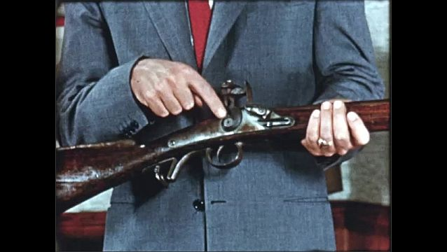 1940s: Man takes gun from rack. Close up, hand touches parts of gun. Exterior of building. Waterfall next to building.