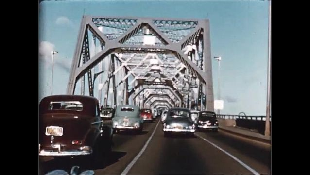 1940s: Close up, train passes camera. Tracking shot, cars driving across bridge. Car driving on highway through city.