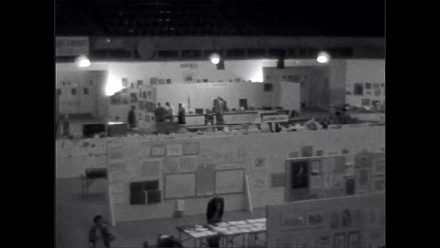 1940s: View from above of an art exhibition. Paintings hang from movable shelves and arranged in rows. People walk in the rows, looking at the art. Tables of exhibits.