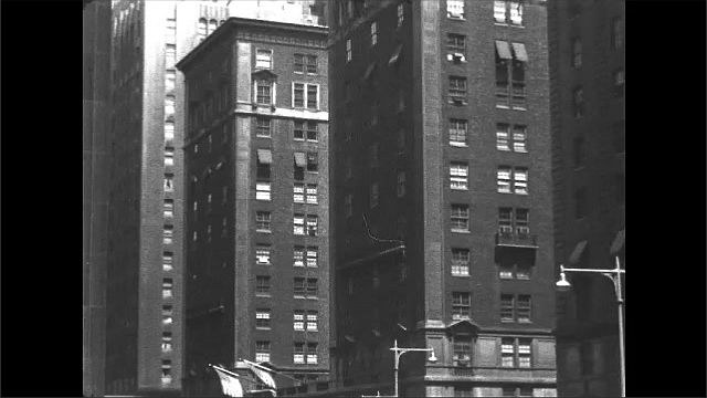 "1940s: Doorman hails cab outside of hotel.  Awning reads ""STARLIGHT ROOF.  THE WALDORF-ASTORIA.""  Pedestrians.  Skyscrapers."