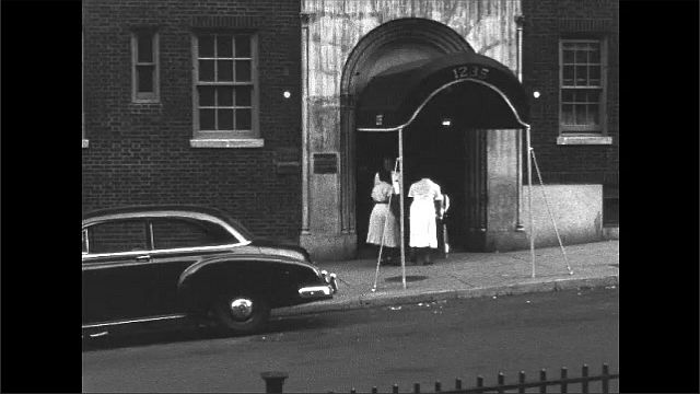 1940s: City street.  Women walk with baby carriage.  Women enter apartment building.