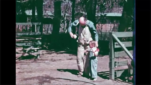 1950s: Father hugs the crying little girl and swings her around, then puts her down. The goats drink from their bucket. The little girl takes the hose again.