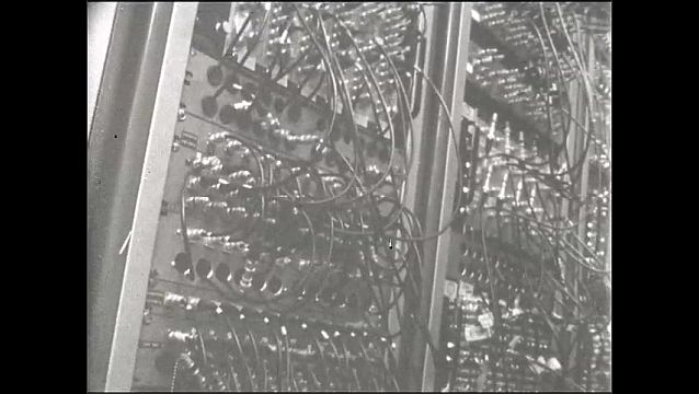 1960s: UNITED STATES: men sit on top of beams. Panels on side of concrete shield. Men look at pipe. Piece of film on pipe