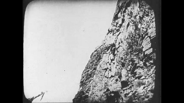 1910s: UNITED STATES: men climb rock face. Climbers on ascent up rock face. Multi pitch climb.