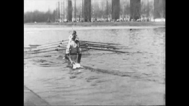 1910s: UNITED STATES: cox instructs rowing boat crew on river. Rowers on water