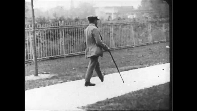 1910s: UNITED STATES: man walks with limp and stick
