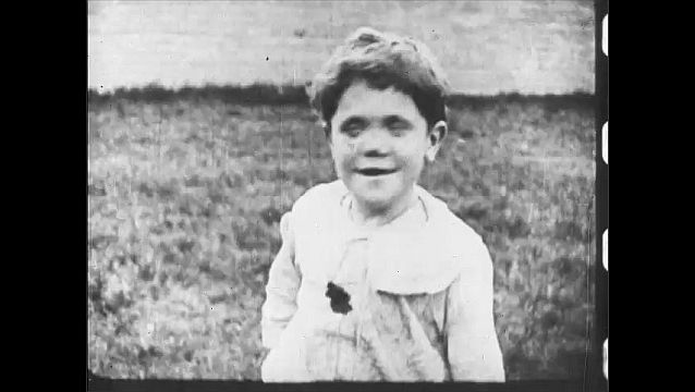 1910s: UNITED STATES: blind girl smiles. Malnourished baby cries.