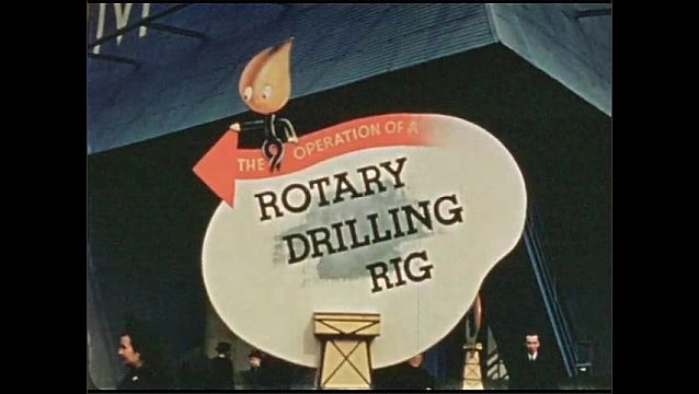 """1930s: American flag on top of oil derrick.  Sign reads """"THE OPERATION OF A ROTARY DRILLING RIG."""""""