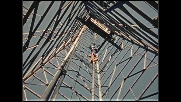 1930s: Man rides drill to top of oil derrick.