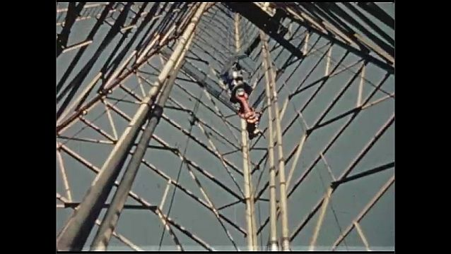 1930s: Men work on oil derrick.  Cable drops down to workers.